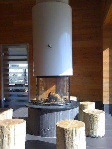 Exemple de réalisations: cheminée circulaire avec le foyer Rüegg modèle ATRIUM et sa hotte métallique blanche.